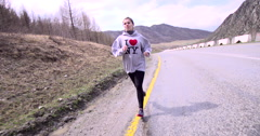 "Girl in a sweater with the inscription ""I love NY"" is running in the mountains - stock footage"