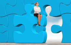Business woman building a blue puzzle on a sky background. - stock photo