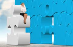 Business woman with a white puzzle on sky background. - stock photo