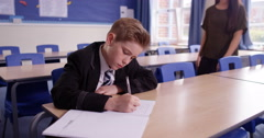 4k, A teacher helping her student one on one with her work in the classroom - stock footage