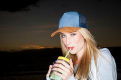 Young woman wearing baseball cap drinking from mason jar looking at camera sm Stock Photos