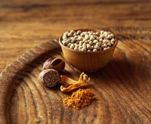 Coriander seeds, mace and nutmeg on wooden plate, close-up - stock photo
