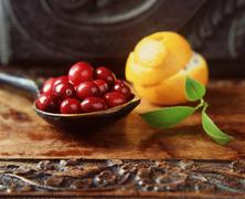 Spoonful of cranberries with orange peel in spiral on wooden table Stock Photos