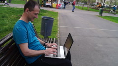 Man with laptop sitting In the park, smilling and chatting - stock footage