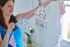 Pregnant woman holding bunting in child nursery - stock photo