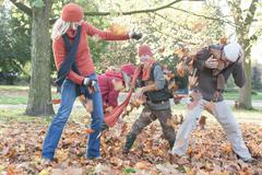 Family fooling around in park, throwing autumn leaves Stock Photos