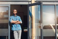 African small business owner standing in the doorway of store - stock photo
