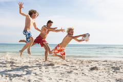 Boy and father chasing brother with rugby ball on beach, Majorca, Spain Stock Photos