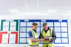 Engineers with digital tablet in front of productivity and safety board in Stock Photos
