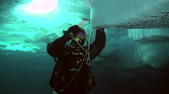 Diver under the Arctic ice at the North Pole takes samples of ice. - stock footage