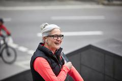Mature woman training in city, listening to earphone music from smartphone Stock Photos
