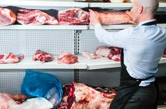 Butcher placing joint of meat on refrigerated cabinet, rear view - stock photo