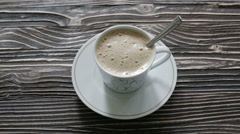 A cup of cappuccino with foam is on the table - stock footage