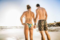 Rear view of mid adult couple wearing shorts and bikini on beach, Cape Town, Kuvituskuvat