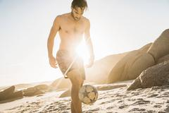 Mid adult man wearing swimming shorts playing soccer keepy uppy on beach, Cape Stock Photos