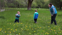 The woman teaches two children to blow on a dandelion, on a flower glade Stock Footage