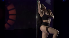 Attractive woman pole dancer performing dance on nightclub lighted stage floor - stock footage