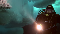 Diver under ice of North Pole with flashlight. Stock Footage