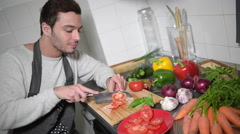 Man chopping vegetables in kitchen and using digital tablet Stock Footage
