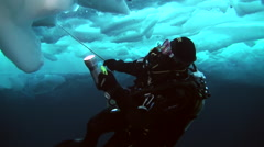 Diver under ice of North Pole with flashlight explores large block Stock Footage