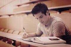 Student sitting reading a book and taking notes - stock photo