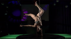 Sexy woman dancer performs sensual pole dance on lighted stage in night club - stock footage