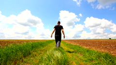 Man with arms outstretched at beautiful European countryside in springtime Stock Footage