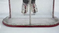 Feet of ice hockey goaltender taking up position in goal crease, protecting net Stock Footage
