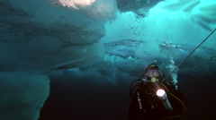 Diver lights the way underwater flashlight. in Arctic at geographic North Pole. Stock Footage