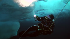 Man lights the way underwater flashlight in Arctic at geographic North Pole. Stock Footage