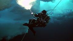 Diver with a flashlight on the ice against the water on the pole. Stock Footage