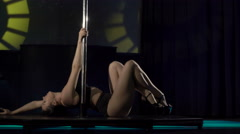 Pole dancing at night club sexy woman dancer performs  dance on lighted stage - stock footage