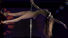 Young woman in sexy lingerie & red chrome platforms performs pole dance on stage Stock Footage