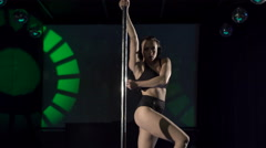 Young woman pole dancer performing sensual dance on lighted stage at night club Stock Footage