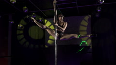 Graceful young woman pole dancer performs sensual dance on lighted stage floor - stock footage