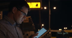 Man with tablet computer on bus station at night Stock Footage