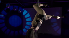 Young woman poledancer performs pole dance tricks on stage at dancing night club Stock Footage