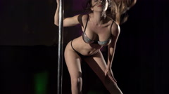Young woman in sexy lingerie performs pole dance on night club lighted stage - stock footage