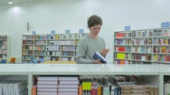 Young Man Taking Book from Bookshelf in Library Stock Footage