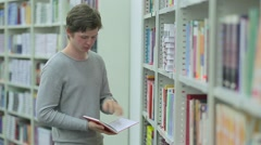 Student Taking Book from Bookshelf in Library Stock Footage