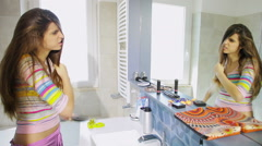 Woman brushing long messy hair in front of mirror in the morning Stock Footage