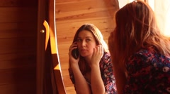 Young woman looks in the mirror Stock Footage