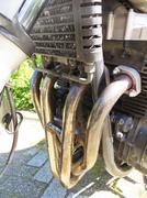 Exhaust system of a four-cylinder engine of a motorcycle - stock photo
