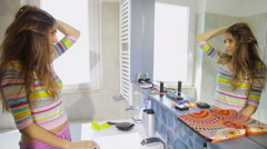 Woman trying to fix messy hair in front of mirror in the morning Stock Footage