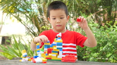 Asian boy build plastic block on wooden table in park Stock Footage