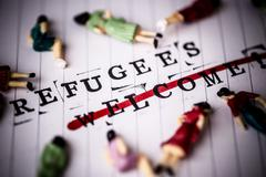 Refugees welcome strikethrough text on white line paper with face off woman f Stock Photos