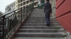 Woman going up stairs wearing coat in the city rear back view Stock Footage