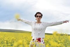 Young woman feeling happy in the middle of a canola field - stock photo