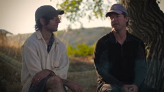 Two middle aged men sit together outside in the wilderness and talk - stock footage