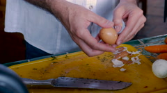 A middle aged man peels a hard boiled egg while working beside his father Stock Footage